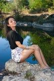 Mooie jonge vrouwenzitting door de rivier Royalty-vrije Stock Fotografie