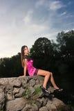 Mooie jonge vrouwenzitting door de rivier stock fotografie