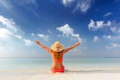 Mooie jonge vrouwenzitting gelukkig op zand, tropisch strand in de Maldiven stock afbeelding