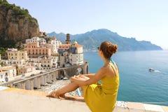 Mooie jonge vrouwenzitting op muur die het overweldigen van panoramisch dorp van Atrani op Amalfi Kust, Italië bekijken royalty-vrije stock foto's