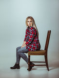 Mooie jonge vrouwenzitting op stoel Royalty-vrije Stock Foto's
