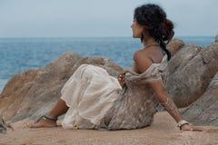 Mooie jonge vrouwenzitting op zand bij het strand stock fotografie