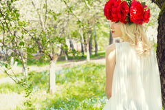 Mooie jonge zachte elegante jonge blonde vrouw met rode pioen in een kroon van witte blouse die in de weelderige appelboomgaard l Stock Fotografie