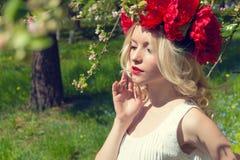 Mooie jonge zachte elegante jonge blonde vrouw met rode pioen in een kroon van witte blouse die in de weelderige appelboomgaard l Stock Foto's