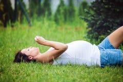 Mooie jonge zwangere vrouw, die in het gras, het maken liggen royalty-vrije stock fotografie