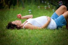 Mooie jonge zwangere vrouw, die in het gras, het maken liggen royalty-vrije stock afbeeldingen