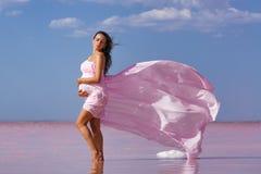 Mooie jonge zwangere vrouw die van de zon op het strand, roze meer genieten stock afbeeldingen