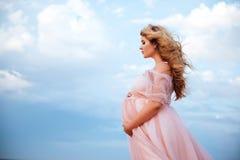 Mooie jonge zwangere vrouw die van de zon op roze meer genieten stock foto's