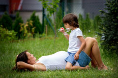 Mooie jonge zwangere vrouw en haar ouder kind, het liggen I stock fotografie