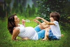 Mooie jonge zwangere vrouw en haar ouder kind, het liggen I stock afbeelding
