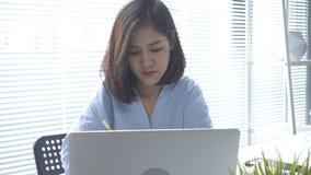 Mooie jongelui die Aziatische vrouw glimlachen die aan laptop werken terwijl thuis het zitten in een woonkamer stock video