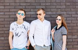 Mooie jongeren die zich tegen bakstenen muur bevinden royalty-vrije stock foto