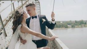 Mooie jonggehuwden die rond op de rand van de brug voor de gek houden stock video