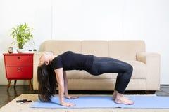 Mooie Kaukasische donkerbruine vrouw in zwarte kleren op blauwe yoga stock afbeeldingen