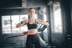Mooie Kaukasische jonge vrouw die hulahoepel in staptaille doen die voorwaartse houding hooping Jonge vrouw die hulahoepel doen stock afbeelding