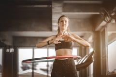 Mooie Kaukasische jonge vrouw die hulahoepel in staptaille doen die voorwaartse houding hooping Jonge vrouw die hulahoepel doen stock foto