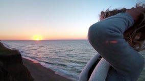 Mooie Kaukasische krullende blonde eenzame jonge vrouw bij zonsopgang of zonsondergang op de oceaankust Verzamelt haar verfomfaai stock video