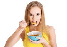 Mooie Kaukasische slanke vrouw die cornflakes eten Stock Foto