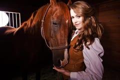Mooie Kaukasische veedrijfster met een paard stock foto