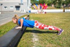 Mooie Kaukasische vrouw die opdrukoefeningen op bank in openlucht, fitness en sportlevensstijl doen Royalty-vrije Stock Foto's