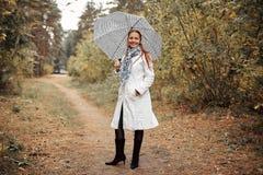 Mooie Kaukasische vrouw op middelbare leeftijd met rood haar met een paraplu in het Park op een bewolkte de herfstdag royalty-vrije stock afbeelding