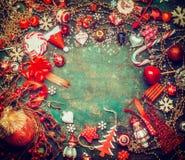 Mooie Kerstmisachtergrond met vakantiesnoepjes, slinger en rode feestelijke decoratie, hoogste mening, kader royalty-vrije stock afbeeldingen