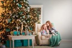 Mooie Kerstmisfoto Twee zusterstweelingen in het verfraaide binnenland tegen de achtergrond van de Nieuwjaarboom Stock Fotografie