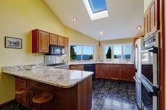 Mooie keukenruimte met de tegelvloer van het dakraamgraniet Stock Afbeeldingen