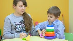 Mooie kinderen die met plastic piramide spelen stock video