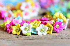 Mooie kinderenarmband op uitstekende houten lijst Armband van kleurrijke plastic bloemen, bladeren en parels wordt gemaakt die stock foto