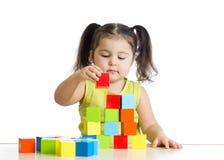 Mooie kindspelen die een kasteel met kubussen bouwen Stock Afbeeldingen