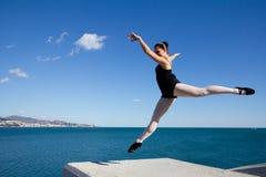 Mooie klassieke danser die over een groot steenblok springen Royalty-vrije Stock Foto's