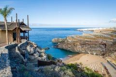 Mooie kleine baai met zandstrand en blokhuis bovenop wandelingsweg aan het stock fotografie
