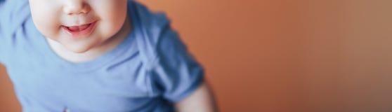 Mooie kleine meisje of jongen die met donker haar op een heldere oranje kleur als achtergrond van 2019 met ruimte voor tekst gelu stock fotografie