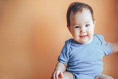 Mooie kleine meisje of jongen die met donker haar op een heldere oranje kleur als achtergrond van 2019 met ruimte voor tekst gelu royalty-vrije stock fotografie