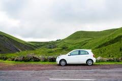 Mooie Kleine witte auto die zich door de wegkant bevinden stock fotografie