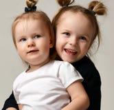 Mooie kleine zusters die koesterend elkaar het gelukkige glimlachen op grijs zitten Royalty-vrije Stock Afbeeldingen