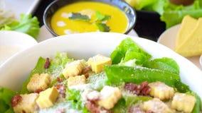 Mooie kleurrijke caesar salade met het kleden van croutons en parmezaanse kaaskaas samen met gele pompoensoep Gezonde Maaltijd stock footage