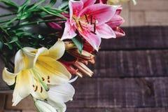 Mooie kleurrijke leliebloemen op houten achtergrond Gele speld royalty-vrije stock foto