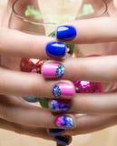 Mooie kleurrijke manicure met bellen en kristallen op vrouwelijke hand Close-up Stock Foto's