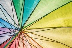 Mooie kleurrijke natte paraplu met doorzichtige zon wordt gezien die van onderaan stock fotografie