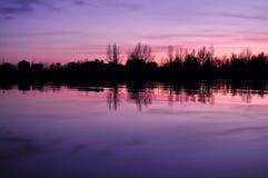 Mooie kleurrijke schemer op een rivier met silhouetten van huizen en bomen Stock Afbeelding