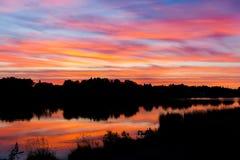 Mooie kleurrijke zonsondergang De hemelflikkeringen in verschillende kleuren Men kan de silhouetten van bomen en huizen zien Royalty-vrije Stock Fotografie