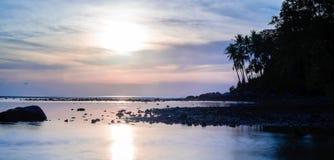Mooie kleurrijke zonsondergang dichtbij het smal eaxotic eiland met palm Stock Afbeeldingen