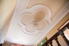 Mooie kroonluchter op een plafond met gipspleister het vormen stock afbeelding