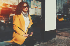 Mooie krullende dame met digitale tablet het wachten bus stock foto
