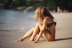 Mooie krullende meisjesrust op strand Stock Afbeeldingen
