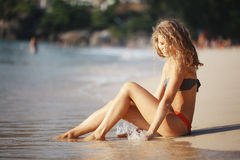 Mooie krullende meisjesrust op strand Stock Fotografie