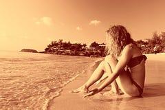 Mooie krullende meisjesrust op strand Stock Afbeelding