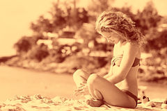 Mooie krullende meisjesrust op strand Stock Foto's